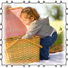 little girl reaching into picnic basket
